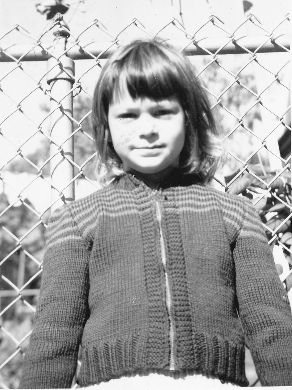June Guralnick as a child in a sweater in front of a chain link fence - black and white photo